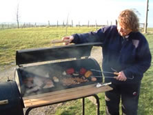 Smoky Jo tensing to smoked peppers, chickens and trout on a barrel smoker